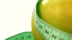 Green, fresh apple with measuring tape on white, rotation, close up Stock Footage