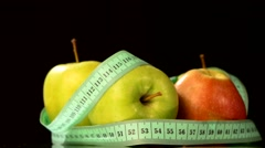 Apple collection with measuring tape, rotation, reflection, on black - stock footage