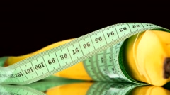Banana wrapped up with measure tape, reflection, rotation, close up, on black Stock Footage