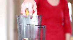 Woman putting fruit into blender - stock footage