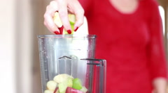 Woman putting fruit into blender Stock Footage