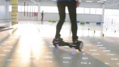 Man and Woman ride balancing Segway motorized scooter io hawk - stock footage