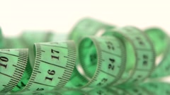 Green measure tape, on white, rotation, reflection, close up Stock Footage