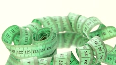 Green measure tape, on white, rotation, reflection, top view Stock Footage