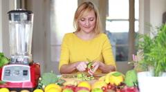Woman peeling skin off kiwifruit - stock footage