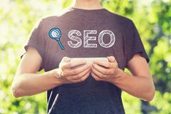 SEO concept with young man holding his smartphone - stock illustration