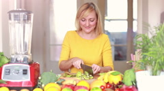Girl slicing kiwi for smoothie Stock Footage