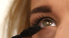 Woman applying mascara on her long eyelashes. close up Stock Footage