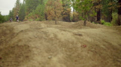 Two cyclist ride over rough dirt terrain Stock Footage