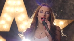 sexy woman singer with microphone, shining star in the background. close up - stock footage