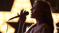 silhouette sexy woman singer with microphone, shining star in the background - stock footage