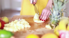 View of woman hands cutting pineapple on small pieces - stock footage