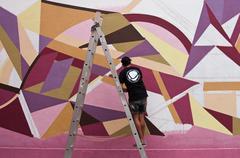 painter artist on graffiti wall with epistrophe ass - stock photo