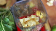 Hands putting pieces of pineapple in blender - stock footage