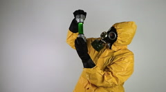 Man in a suit of chemical protection examines a liquid substance - stock footage