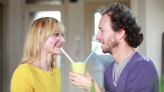 Couple drinking smoothie from same drinking glass - stock footage