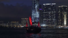 Oriental style red sail traditional boat in Hong Kong bay at night passing by Stock Footage
