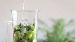 Pouring water in blender with fruits and vegetables - stock footage