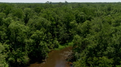 Flight above a winding brown river in a forested Alabama swamp Stock Footage