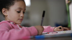 Young girl colours in with her coloured pens and a book Stock Footage