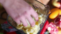 Hand putting avocado in blender with pineapple - stock footage