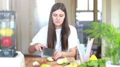 Woman chopping apple on wooden board - stock footage