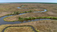 Flight over a meandering waterway through marshy grasslands Stock Footage