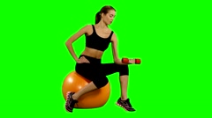 Girl sitting on pilates ball and exercising with dumbbells. Green screen Stock Footage