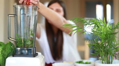 Woman putting carrot and pouring water into blender - stock footage