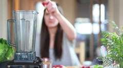 Woman putting fruits in blender for blending - stock footage