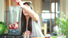 Woman pouring water into blender with fruits - stock footage