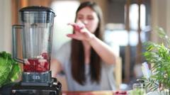 Woman blending fruits in blender - stock footage