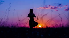 Silhouette of a Young Girl Practicing Yoga Tree Pose At  Sunset Stock Footage