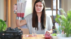 Woman pouring fruit smoothie into glass and drinking it - stock footage