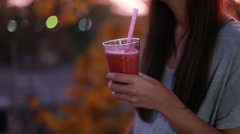 Young woman drinking fruit smoothie Stock Footage