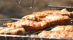 Grilled steaks over flames and coals, on the brazier, turn slices, close up Stock Footage