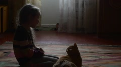 Little Girl is Patting The Orange Tabby Cat Animal is Hervous Girl With Long Stock Footage