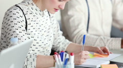 Woman writing in notebook during business meeting, male colleague in background Stock Footage