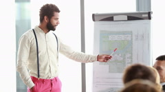 Handsome man pointing at flipchart while giving presentation to his colleagues Stock Footage