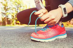 Female jogger tying her running shoes for a jog - stock photo