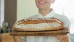 A young smiling woman holding freshly baked bread, close up HD Stock Footage
