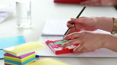 Stock Video Footage of Woman hand taking notes in puzzle notebook during a meeting