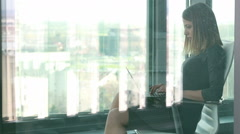 Businesswoman typing on laptop while sitting on chair behind glass wall Stock Footage