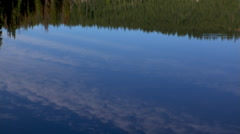Forest and clouds reflected in the calm surface of a mountain lake Stock Footage