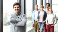Portrait of male advertising executive smiling, colleagues in background - stock footage