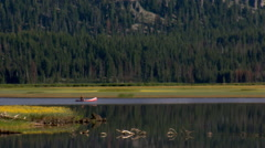 Canoeist on a mountain lake bounded by grassy meadows with forest in background Stock Footage