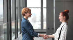 Two female advertising executives shaking hands - stock footage