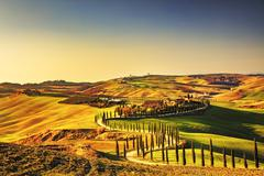 Stock Photo of Tuscany, Crete Senesi rural sunset landscape. Countryside farm, cypresses tre