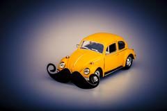 yellow car with mustache, beetle on white,male version of hippie car, movembe - stock photo