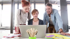 Female creative executive discussing a new project on laptop with team - stock footage